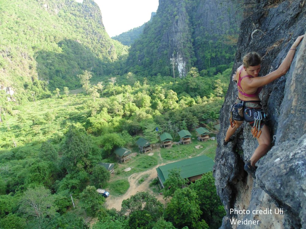 Kletterin am Fels mit Blick auf das Retreat Gelände